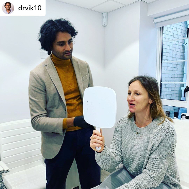 Woman looking into a hand held mirror with a men next to her