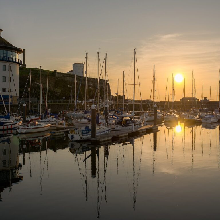 Sail boats in a port with the sun setting